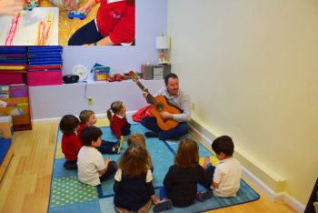 preschoolers listening to the teacher playing guitar