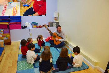 preschoolers listening to the teacher playing guitar